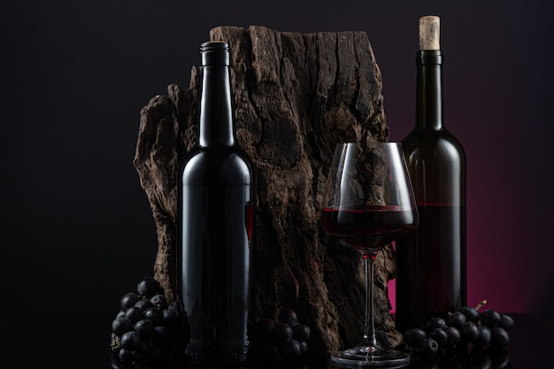 Bottles, glass of spanish red wine and grapes on  wooden base
