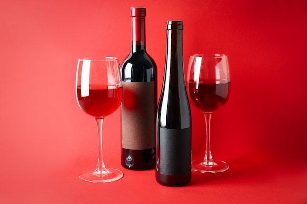 Bottles and glasses of wine on red background