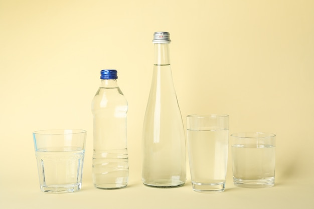 Bottles and glasses with water on beige