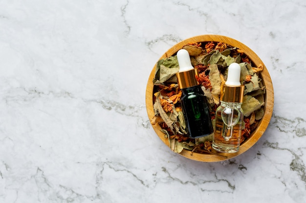 Bottles of herbal spa treatment oil put in wooden bowl