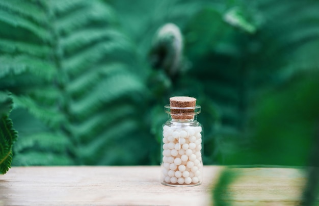 Bottles of homeopathic globules on green fern background. homeopathy medicine.
