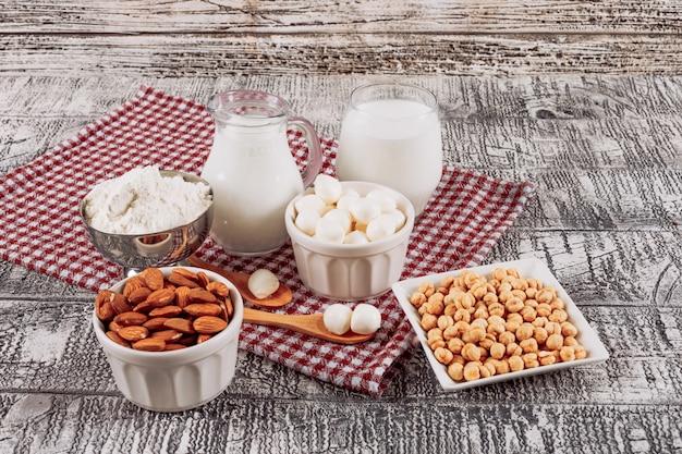 Bottiglie di latte con formaggio e cucchiaio di legno, mandorle, vista dell'angolo alto della nocciola su un fondo di legno grigio
