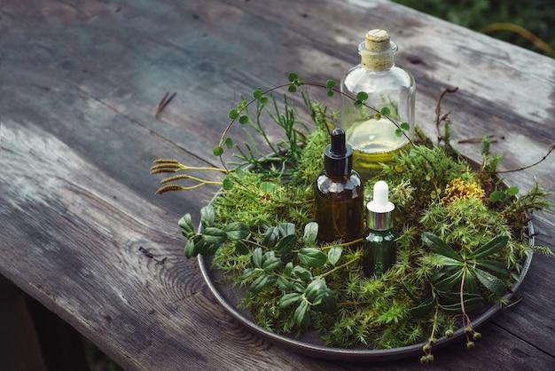 ボトル天然化粧品美容液、木製テーブルに新鮮な植物とチンキ油