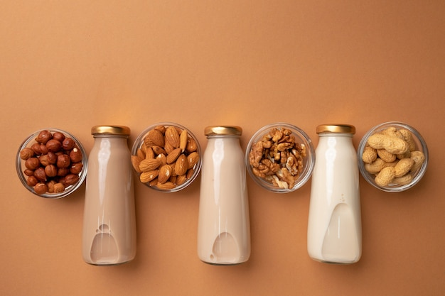 Bottles of nut non dairy milk on brown