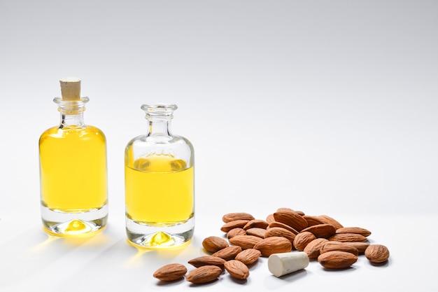 Бутылки миндального масла и миндалин на белой предпосылке, copyspace.