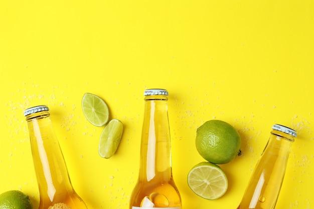 黄色の背景にビール、ライム、塩のボトル