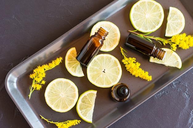 黒の背景とフルーツスライスに柑橘系のフルーツエッセンシャルオイルのボトル。アロマテラピー、抗ストレス効果。