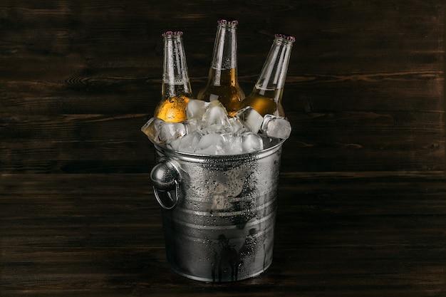 나무 배경에 있는 얼음 조각에 차가운 맥주 한 병