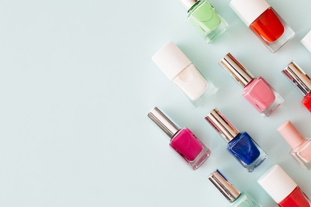 Бутылки красочного лака для ногтей на пастельно-синем фоне. концепция маникюра и педикюра. плоская планировка, вид сверху, копия пространства.