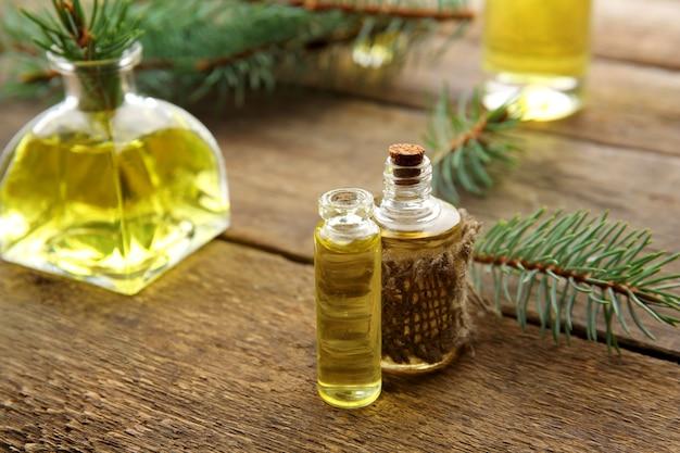 Бутылки хвойного эфирного масла и ветки на деревянном столе, вид крупным планом