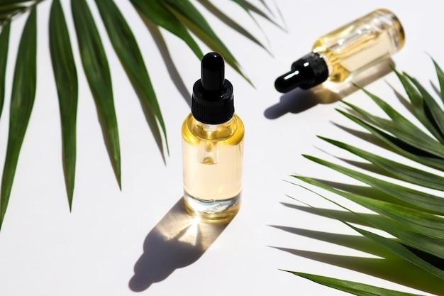 化粧品エッセンシャルオイルとヤシの葉のボトル美容コンセプトセラムスキンケア製品