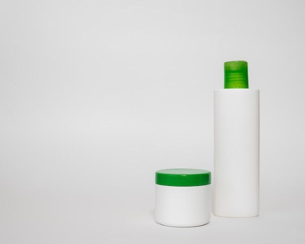Бутылки косметики на белом фоне крем-маска для лица