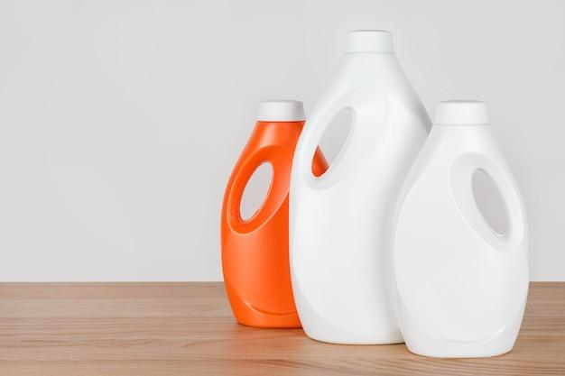 Бутылки моющего средства и кондиционера для белья на деревянном столе, емкости с моющими средствами, жидким моющим средством и кондиционером.