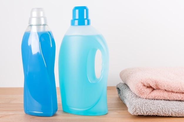 Бутылки с моющим средством и кондиционером для белья с чистыми полотенцами на деревянном столе