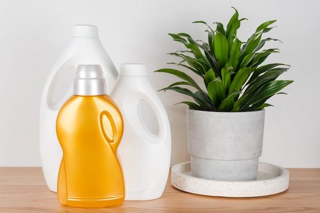 Бутылки моющего средства и кондиционера для белья с зеленым домашним растением в бетонном горшке на столе, контейнеры для чистящих средств