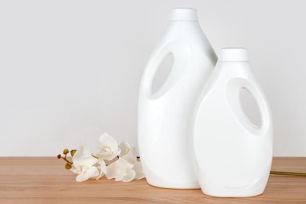 Бутылки моющего средства и кондиционера для белья с белыми цветами орхидеи на деревянном столе, контейнеры чистящих средств