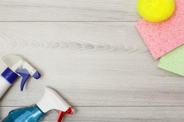 中央にコピースペースがある灰色の木製の背景を掃除するための洗剤、カラーマイクロファイバーナプキン、合成スポンジのボトル。クリーニングツールと機器のセット