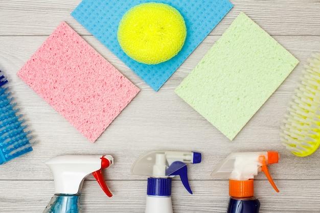 洗剤のボトル、カラーマイクロファイバーナプキン、合成スポンジ、灰色の木製の背景を掃除するためのブラシ。クリーニングツールと機器のセット