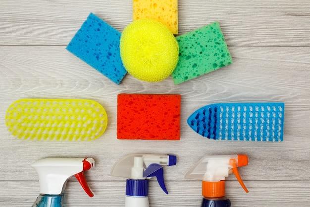 洗剤のボトル、クリーニング用のカラー合成スポンジ、灰色の木製の背景にダストブラシ。クリーニングツールと機器のセット