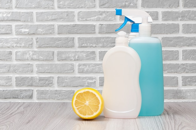 Бутылки жидкости для мытья посуды и лимона с серой стеной на заднем плане.