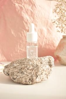 白いテーブルの上のガラス瓶の中のエッセンシャルオイルのボトル。自然化粧品のコンセプトであるアロマセラピーオイル。