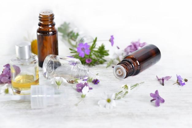 Бутылки эфирного масла и разноцветные лепестки цветов на белом столе