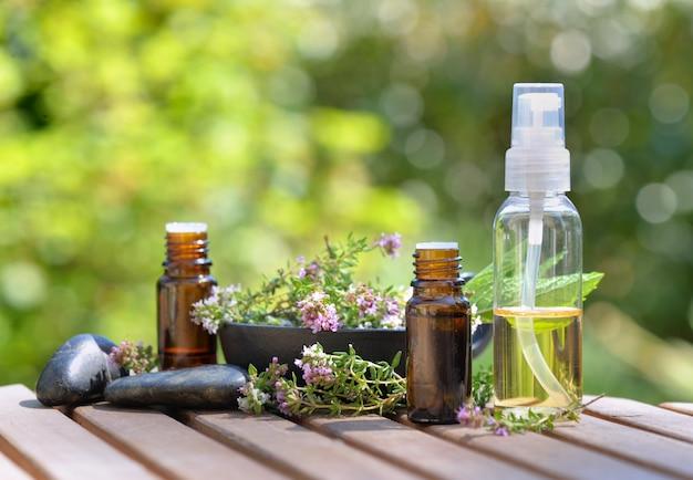 Бутылки эфирного масла и цветов ароматической травы на столе и на зеленой стене