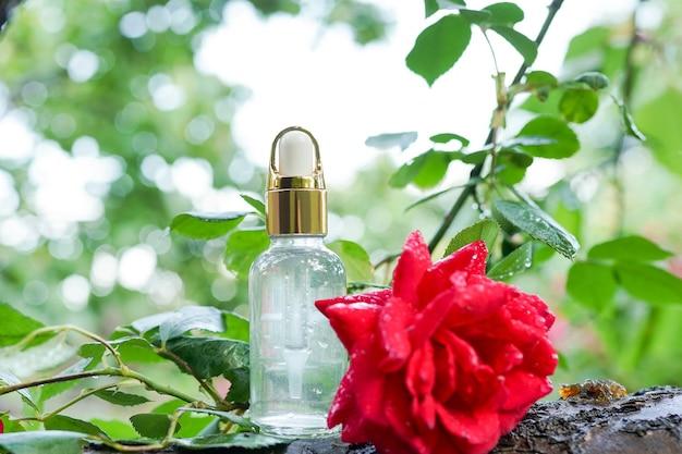 エッセンシャルオイルとピンクのバラのボトルが木の上に。