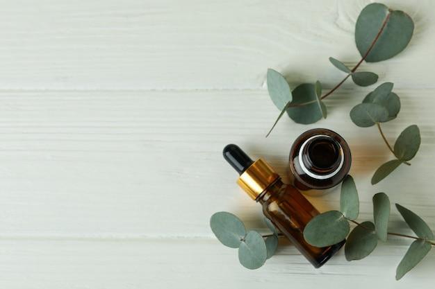 Бутылки эвкалиптового масла и веток на белом деревянном фоне