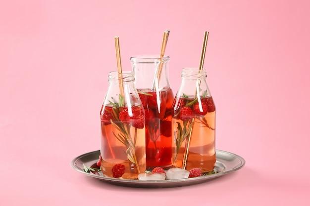Бутылки свежего холодного чая на розовом