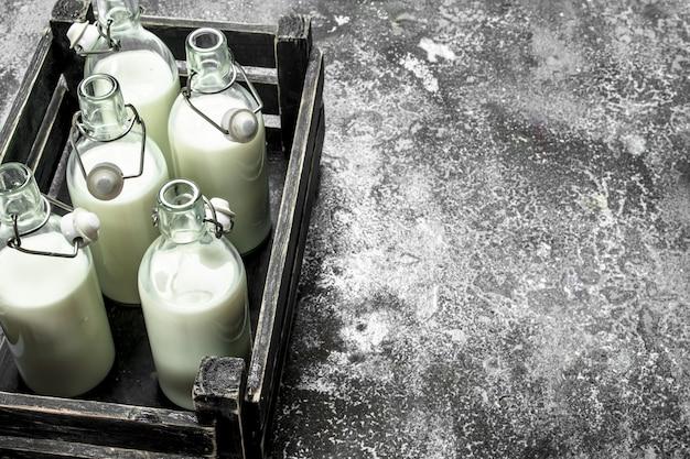 古い箱に入った新鮮なミルクのボトル。