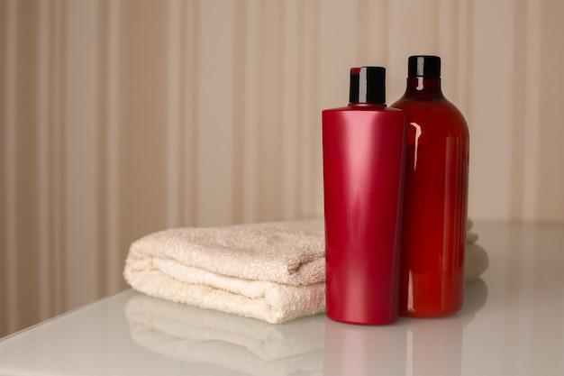 ニュートラルベージュの背景の上に机の上にタオルでヘアシャンプーとバスフォームのボトル。テキスト用のスペース