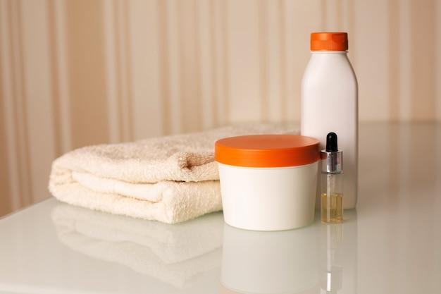 ニュートラルベージュの背景の上に机の上にバスタオルとヘアシャンプー、美容液、コンディショナーのボトル。テキスト用のスペース