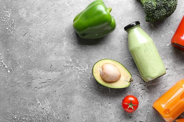 灰色の表面にさまざまな野菜が入った健康的なスムージーのボトル