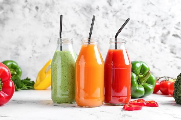 軽い表面にさまざまな野菜が入った健康的なスムージーのボトル