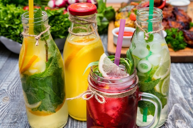 Бутылки домашнего лимонада или коктейля мохито с лимоном, лаймом и мятой, холодный освежающий напиток или напиток со льдом. крупный план. выборочный фокус
