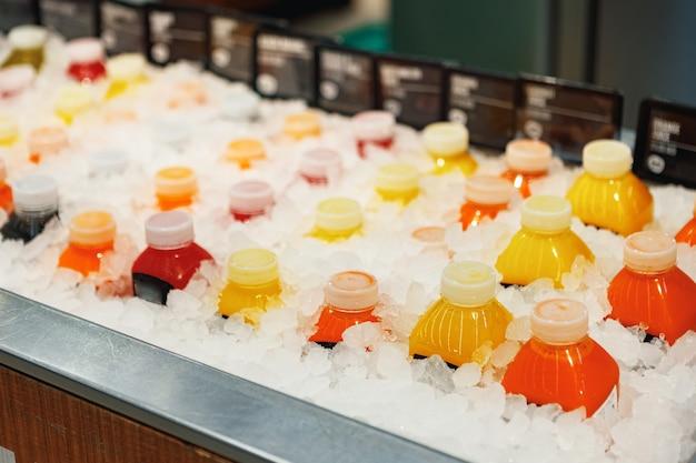 スーパーマーケットの氷のカウンターの上のジュースのボトル