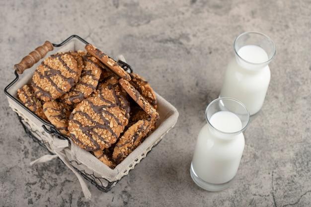 石のテーブルに置かれたバスケットにクッキーとミルクのボトル。