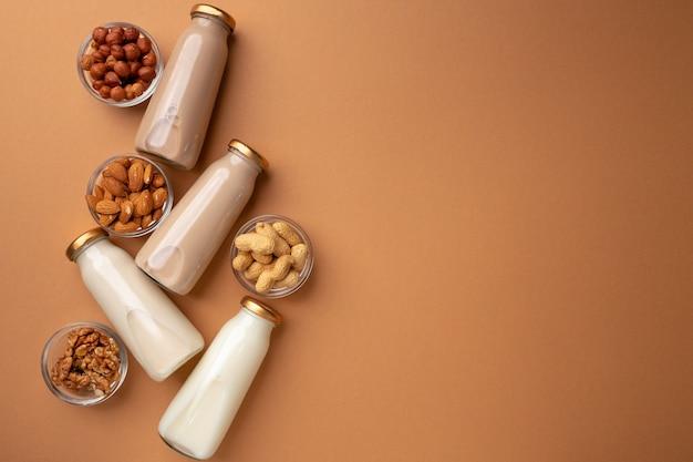 Бутылки орехового немолочного молока на коричневом фоне flatlay