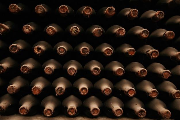 ほこりっぽいセラーの古いワインのボトルワインセラーの古いボトル Premium写真
