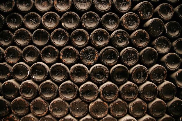 ほこりっぽいセラーの古いワインのボトルワインセラーの古いボトル