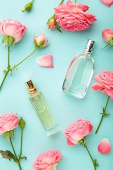 Флаконы духов с розовыми розами на мятой.