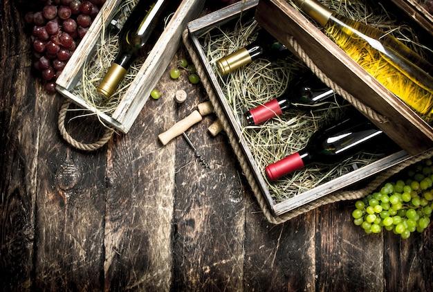 나무 테이블에 오래 된 상자에 빨간색과 흰색 와인 병.