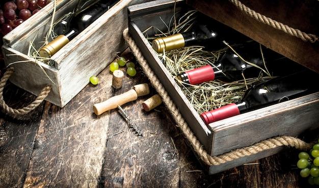 木製のテーブルの上の古い箱に赤と白ワインのボトル。