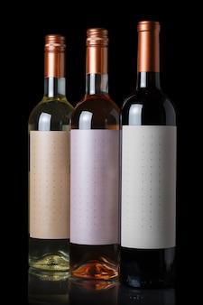 黒の壁に分離された赤、白、ロゼワインのボトル。