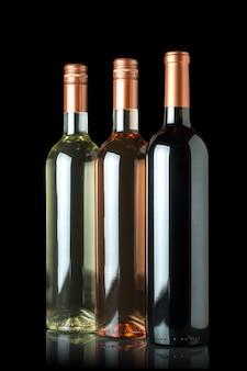 黒の背景に分離されたタグのない赤、白、ロゼワインのボトル。