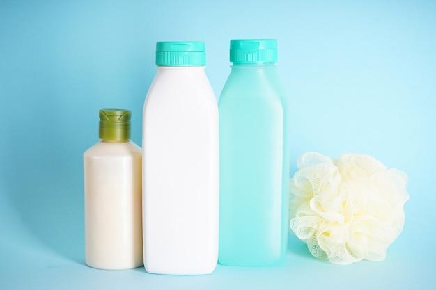 Бутылки шампуня или кондиционера для волос с мочалкой на синем фоне