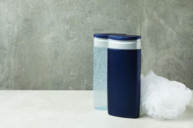 灰色の孤立した背景に対してシャワージェルと手ぬぐいのボトル Premium写真