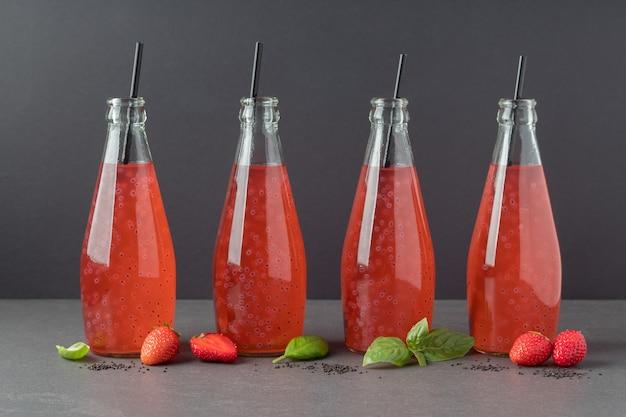 Бутылки клубничного напитка с семенами базилика на сером столе модный напиток для похудения