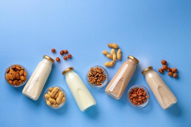 Бутылки веганского немолочного молока с различными орехами на синем фоне, вид сверху